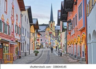 GARMISCH-PARTENKIRCHEN, GERMANY - JANUARY 06, 2015: Cozy narrow street of Garmisch-Partenkirchen (Germany) with the steeple of Maria-Himmelfahrt (Assumption day) church. Selective focus.