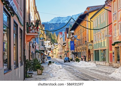 Garmisch-Partenkirchen, Germany - January 6, 2015:  Chalets in Bavarian style decorated for Christmas at Garmisch Partenkirchen old town, Germany. People on the background