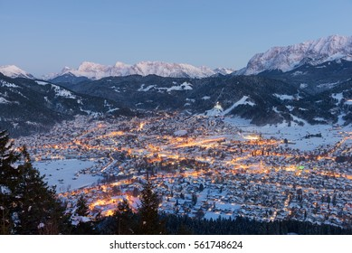 Garmisch-Partenkirchen with snow and mountains in the background at sunset, Bavaria, Germany