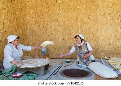 GARNI, ARMENIA - APRIL 27, 2017: Armenian local women make armenian bread known as lavash, in Garni, Armenia.