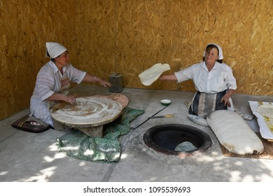 GARNI, ARMENIA, SEPTEMBER 25, 2017. Two women make lavash (a traditional flatbread) by rolling out the dough, then baking in a tandoor oven.