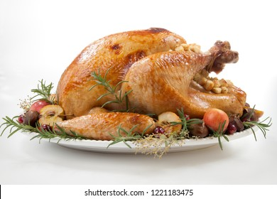 Garnished roasted turkey with grab apples, sweet chestnut, and cranberry over white background