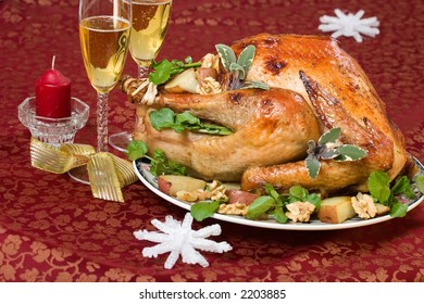 Garnished turkey on Christmas decorated table with candle and flutes of champagne on background