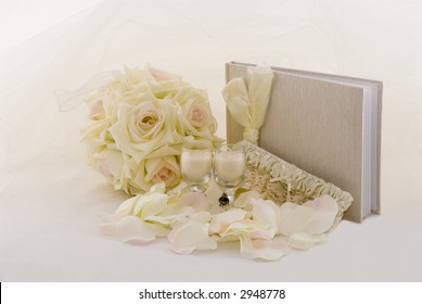 Garter, champagne glass candles, guest book, fabric flower bouquet with a veil as a background