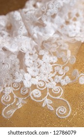 Garter from a fabric embroidered by a satiny lace