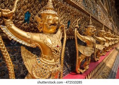 Garuda Wat Phra Kaew Bangkok Thailand - A line of ornate golden demons at the Grand Palace in Bangkok, Thailand