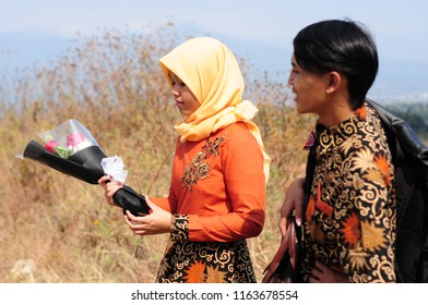 Garut, Indonesia - August 12 2018: Seen a pair of lovers with a bunch of flowers in the hands of her woman.