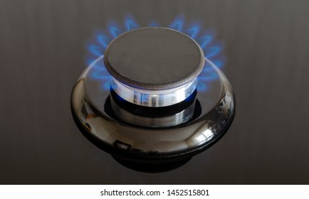 Gas burner with a flame on the stove with a glass surface. Frontal close-up shot, full frame