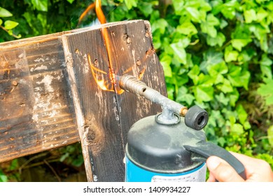 gas burner with hot flame on a wooden pallet to flame it down