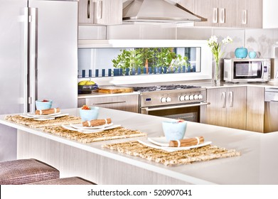 Gas cooker attached to wall, kitchen items with modern furniture and walls, ceramic cups also fruits on the table, floor is tiled, flower vase next to gas cooker, perfect lightning.