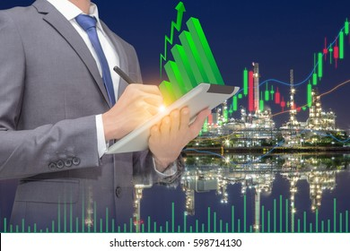 Gas and crude oil stock market with chart indicator and volume information, broker used touch pad for trading commodity and background is onshore refinery.