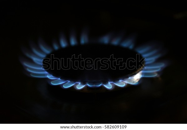 Gas flame on domestic stovetop in the dark closeup