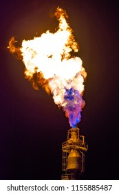 A gas flare at an oil refinery at night.