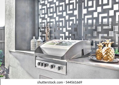 Gas grill cabinet closeup of a modern patio outdoors on the counter top beside an art window, there is a gold color vase, luxury home outside garden.