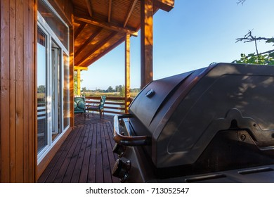 Gas grill on wooden terrace for sunny days, lovely weekends and delicious food. BBQ with friends.