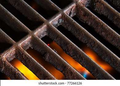 A gas grill with open flames below the rusty iron grate.