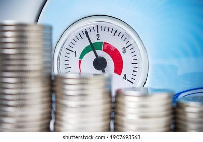 Gas heating boiler pressure gauge near coins. Natural gas saving, energy efficiency concept image.