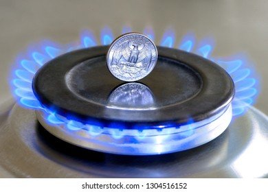 Gas hob with burning natural gas and quarter US dollar coin. The concept of the struggle for global gas markets. Turk stream. North stream
