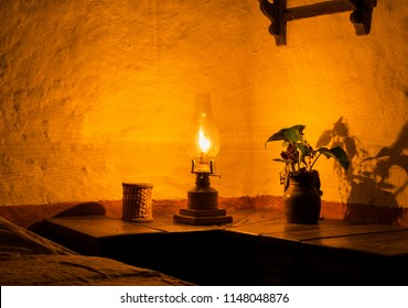 Gas lamp with protective glass casts light on a wall corner, with flower vase and bedside table.