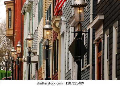 Gas lamps are lit in front of historic row houses