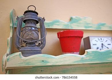 Gas lantern, pot and retro alarm clock on an old shelf