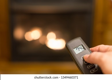 Gas log fireplace being turned on with a remote control that shows the temperature of the room.