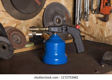 Gas manual blowtorch stands on a workbench in a home workshop grinding wheels and tools in the background blurry