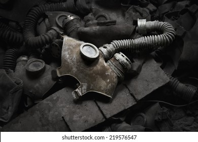 Gas mask in a dark room surrounded by other gas masks.