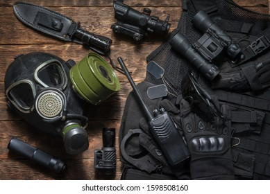 Gas mask, rifle, radio station, binoculars, handcuffs, knife on the special force agent table concept.
