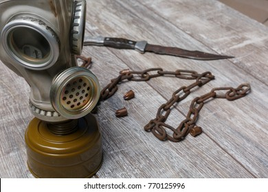A gas mask stands next to a chain on a wooden background