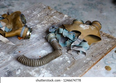 Gas masks on wooden table at school in dead abandoned ghost town of Pripyat in Chernobyl NPP alienation zone, Ukraine
