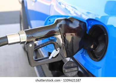 gas nozzle pumping gas in car
