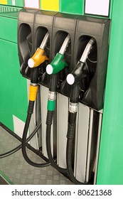 Gas nozzles at the gas station A row of 3 different gas pumps black yellow and green