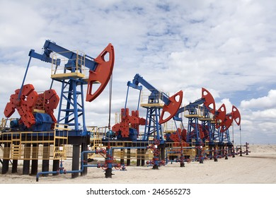 Gas and oil industry. Work of oil pump jack on a oil field. White clouds, blue sky, desert