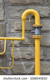 Gas pipe with a valve on the background of the stone wall of the house - Shutterstock ID 1068545810