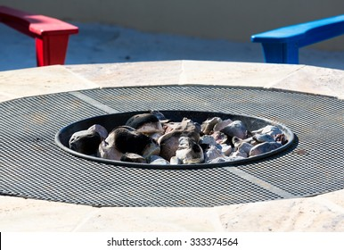 Gas or propane powered firepit with white hot coals and rocks and relaxing chair