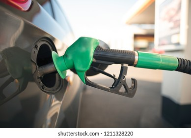 Gas pump nozzle in the fuel tank of a gray car. Refueling the vehicle at a gas station