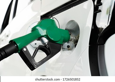 Gas pump nozzle in the fuel tank of a white car.