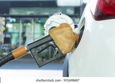 Gas pump nozzle in the fuel tank of a white car, refuel