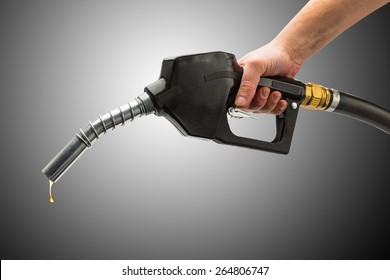 gas pump nozzle with hand and petrol drop on black background