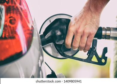 Gas pump person pumping fuel filling car tank at gas station. Man hand holding nozzle refuel. Price of gasoline.