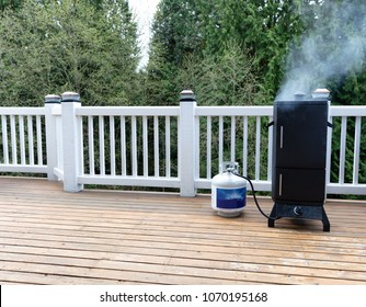 Gas smoker on cedar outdoor deck with woods in background