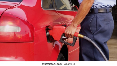 Gas station worker filling up car with fuel, closeup