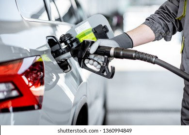 Gas station worker refueling car with gasoline, close-up view focused on the filling gun