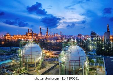 Gasspeicherbehälter und Rohrleitungen in der Öl- und Gasraffinerienanlage mit glatter Lichtbefeuerungsanlage bei Dämmlicht