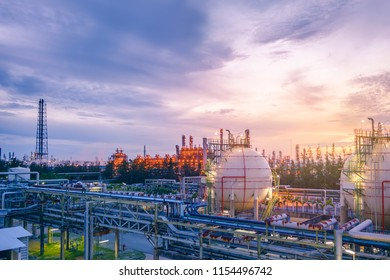 Gas storage sphere tanks and pipeline in oil and gas refinery industrial plant on sky sunset background