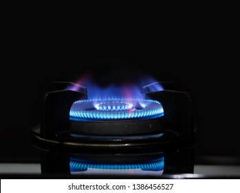 Gas stove burner with blue flames and dark background.