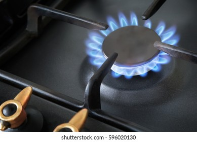 Gas stove with included burner, blue flame natural gas burning.