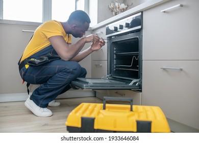 Reparatur von Gasherden. Dunkelhäutiger Servicemann in gelbem T-Shirt zur Reparatur des Gasherdes