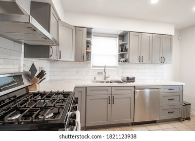 gas stove top and hood fan in a small kitchen with white back splash